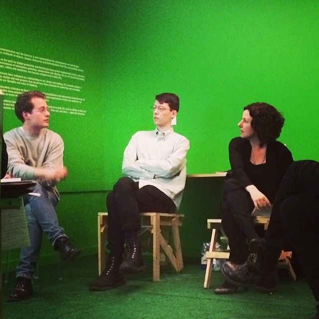 Mara Mills is sitting in a chair in a green room at the Museum of Arts and Design, facing left toward two seated men with whom she is having a conversation. Illegible text is screened on a wall behind one of the men.